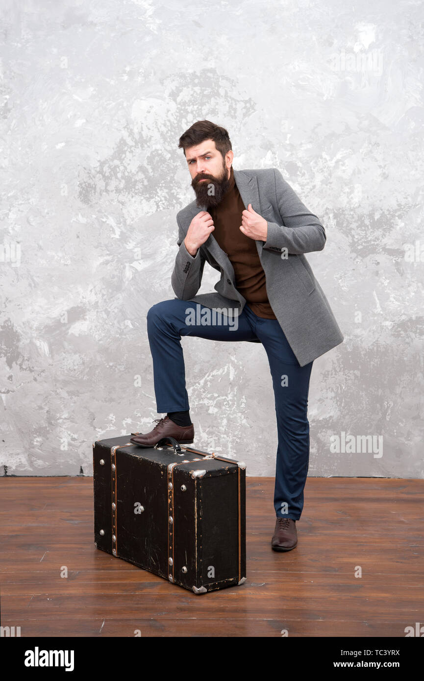 Best travel bags for men. Guy well groomed elegant bearded man and vintage suitcase. Time traveller concept. Vintage inspired design of bag. Retro and vintage. Fashion trend. Accessories for vacation. Stock Photo