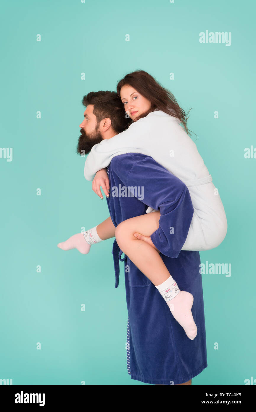 Reliable support. Handsome young man piggybacking beautiful woman. Couple in bathrobes having fun. Trust and support. True love. Lets stay at home. They are closest people. Support in any time. - Stock Image