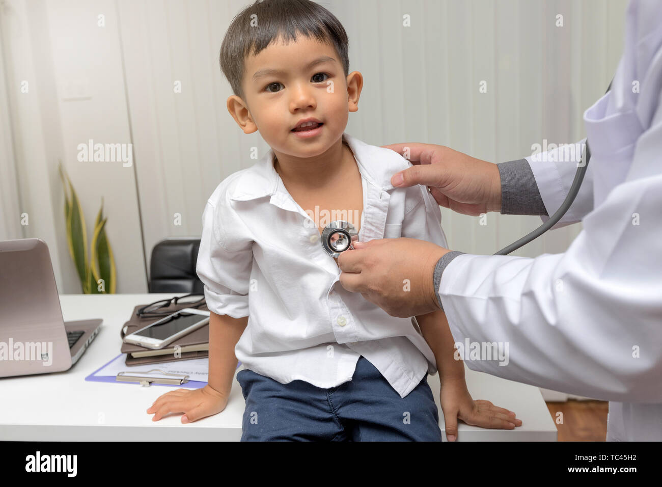 Pediatrician is diagnosing little patient using a stethoscope - Stock Image