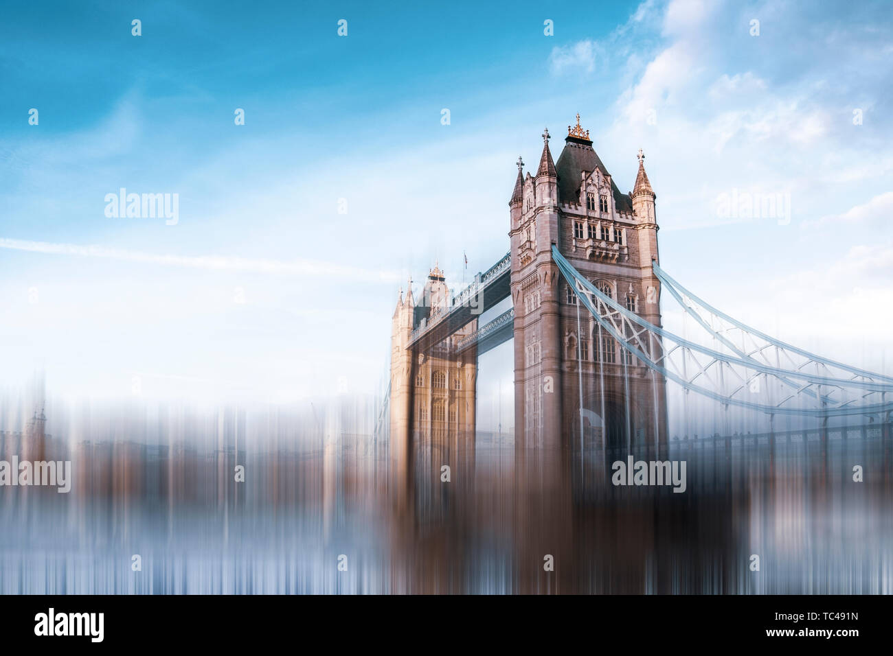 Tower Bridge, one of London's famous bridges and one of many must-see landmarks in London. Blurry speed effect applied to suggest a fast-paced environ - Stock Image