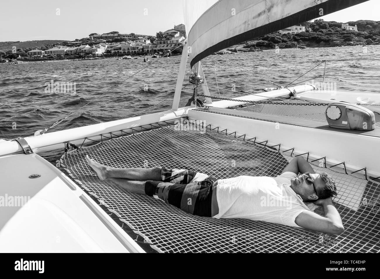 Sporty man relaxing, lying in hammock of a catamaran sailing boat on luxury nautic vacations near picture perfect Palau town, Sardinia, Italy. Black a - Stock Image