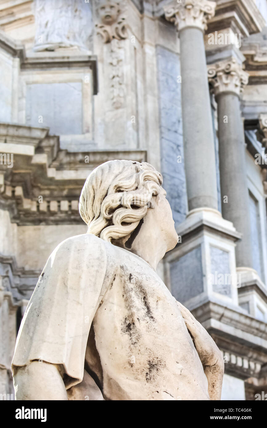 Closeup photography of Antique statue on Baroque Catania Cathedal, Sicily, Italy. The Duomo cathedral is blurred in the background. Marble sculpture. - Stock Image
