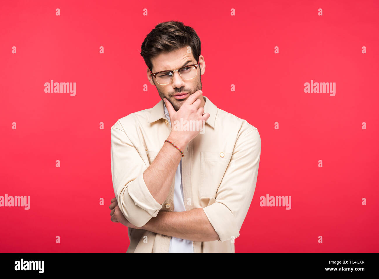 pensive man in glasses touching chin isolated on pink - Stock Image