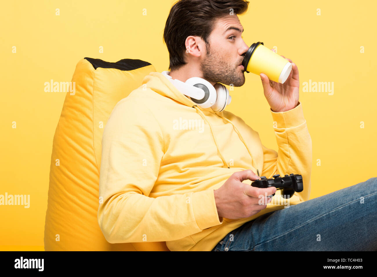 man drinking coffee to go on bean bag chair and playing Video Game Isolated On yellow - Stock Image