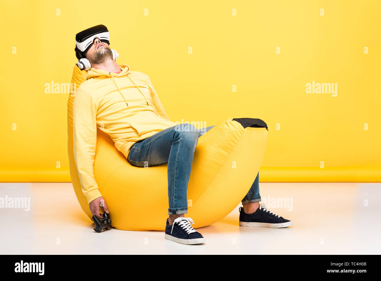 man on bean bag chair with joystick in virtual reality headset on yellow - Stock Image