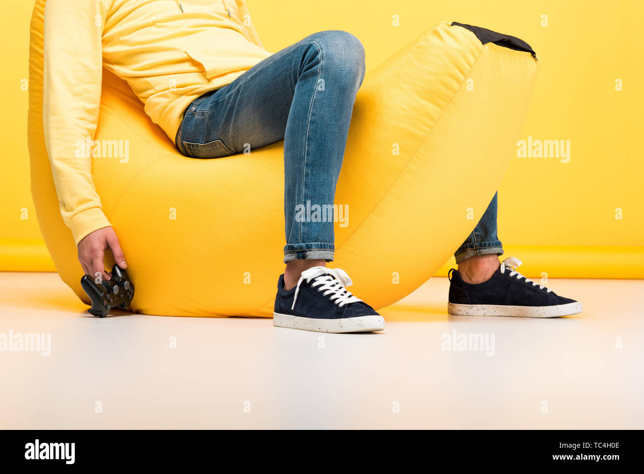 Cropped view of man sitting on bean bag chair with joystick - Stock Image