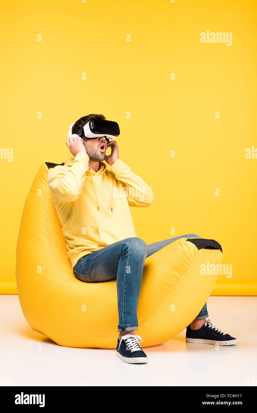 excited man on bean bag chair in virtual reality headset on yellow - Stock Image