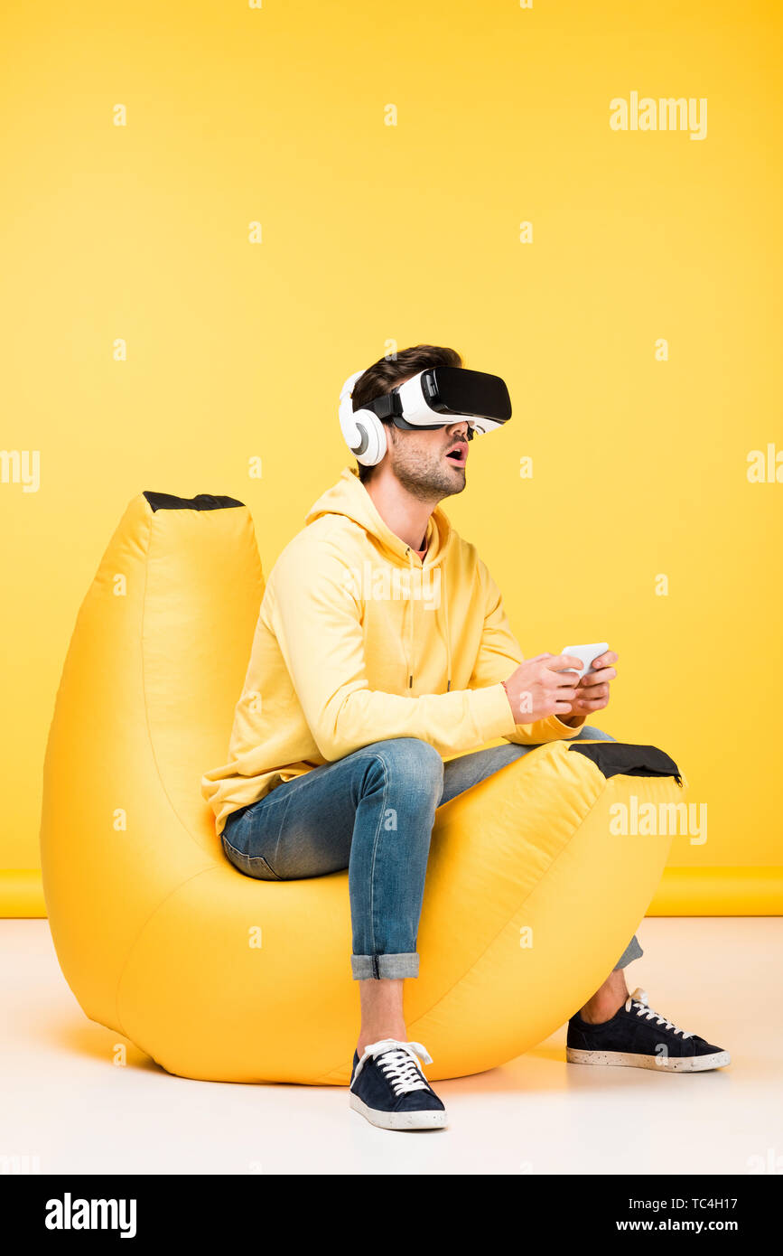 excited man on bean bag chair with smartphone in virtual reality headset on yellow - Stock Image