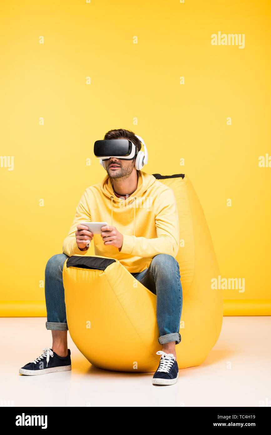 man on bean bag chair with smartphone in virtual reality headset on yellow - Stock Image