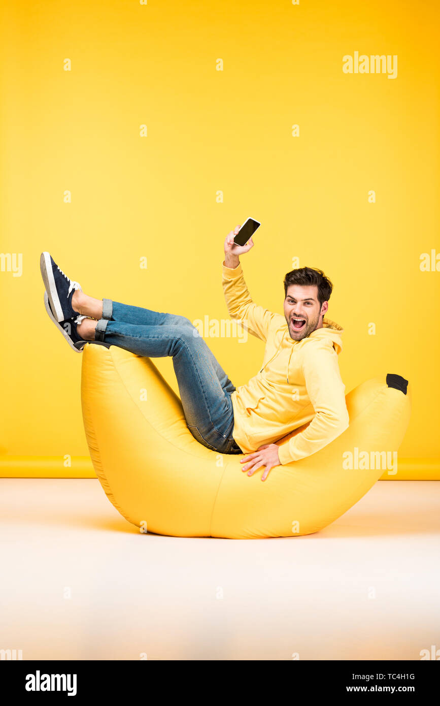 happy man on bean bag chair holding smartphone on yellow - Stock Image