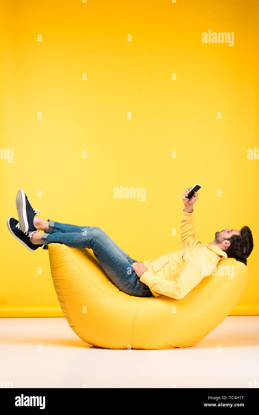 man on bean bag chair taking selfie on smartphone on yellow - Stock Image