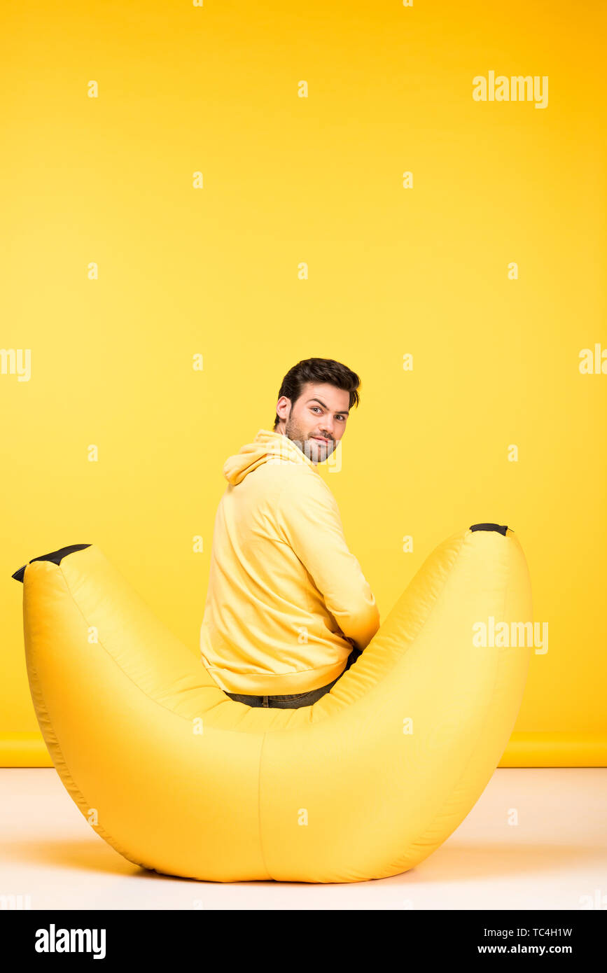 man sitting on bean bag chair on yellow and looking at camera - Stock Image