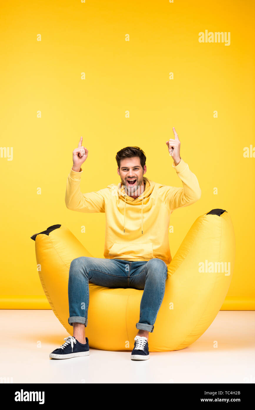excited man on bean bag chair pointing with fingers on yellow - Stock Image