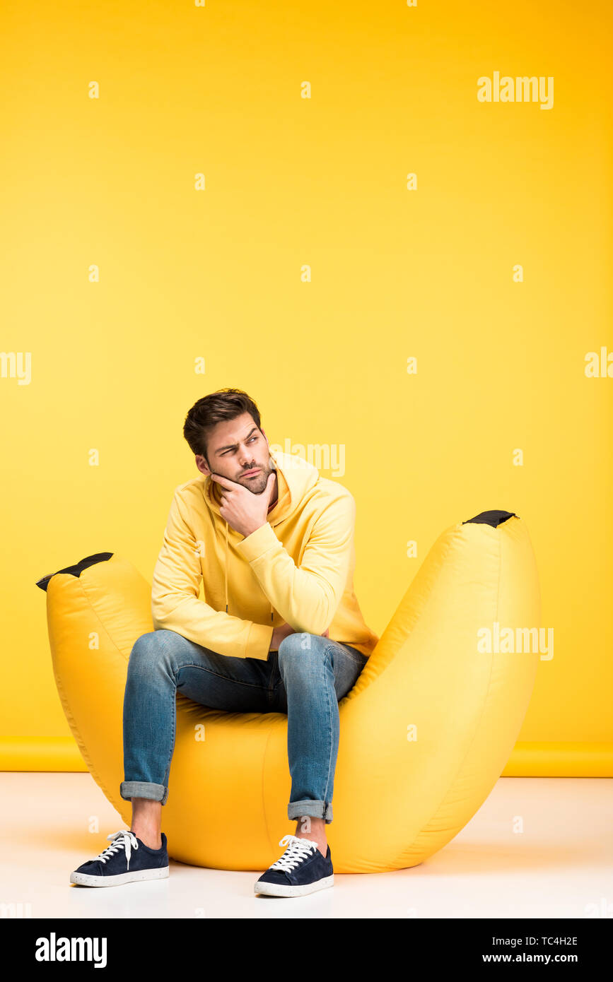 pensive man on bean bag chair touching chin on yellow - Stock Image