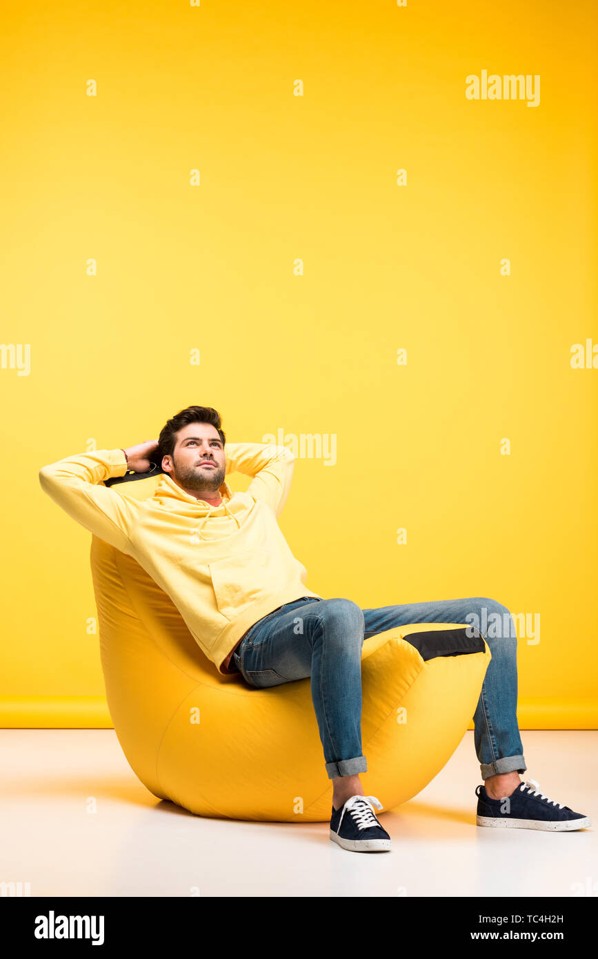 man with Hands Behind Back relaxing on bean bag chair on yellow - Stock Image