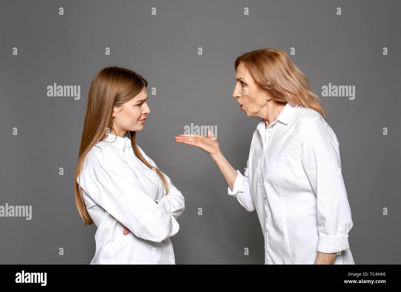 Quarreling mother and daughter on grey background - Stock Image