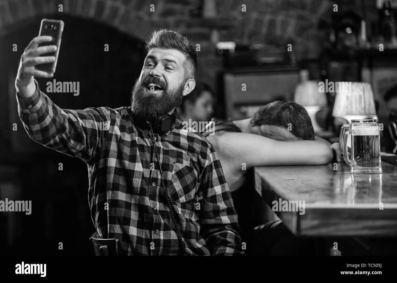 Taking selfie concept. Online communication. Send selfie to friends social networks. Man in bar drinking beer. Take selfie photo to remember great evening in pub. Man bearded hipster hold smartphone. - Stock Image