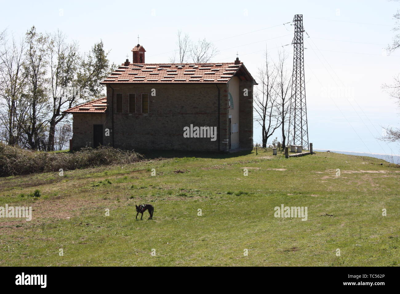 small church abandoned, in disuse, on the Apuan Alps of the Tuscan Apennines in a clearing on a sunny spring day - Stock Image