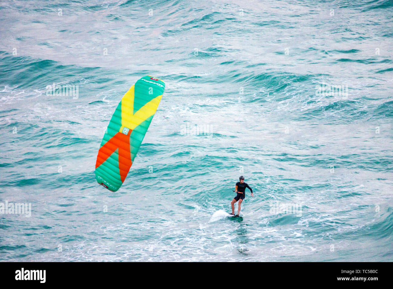 Miami Beach Florida Atlantic Ocean kiteboarding kiteboarder kitesurfing kitesurfer watersports man waves water - Stock Image