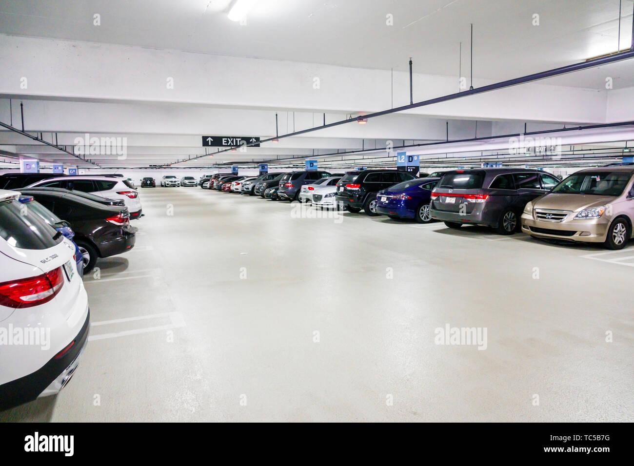 Miami Florida Midtown public parking garage interior parked cars vehicles exit sign - Stock Image