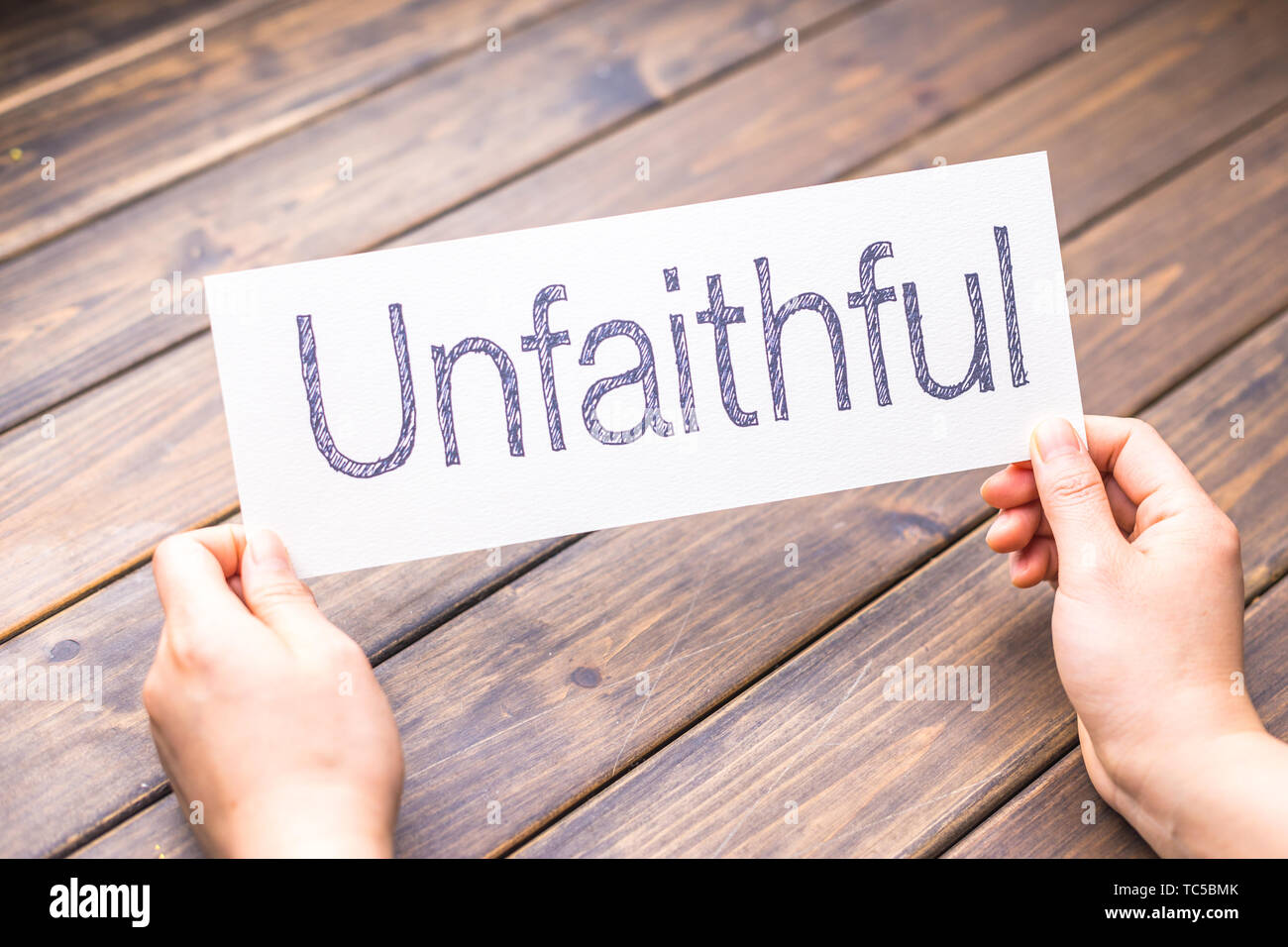 hands hold white paper with word unfaithful - Stock Image