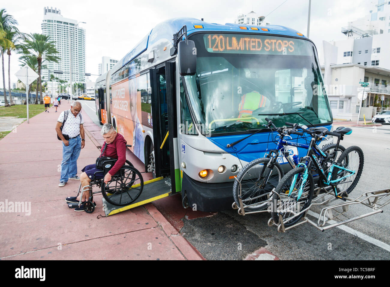 Miami Beach Miami Florida-Dade Metrobus public bus transportation disabled man handicap handicapped ADA access ramp wheelchair bicycle rack - Stock Image