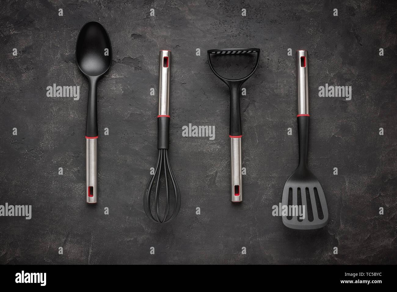 Modern Black Plastic Kitchen Utensils on Dark Background - Stock Image