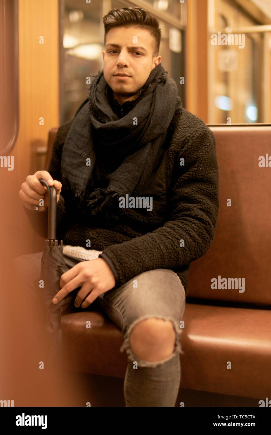 young man, Afghan ethnicity, sitting in underground train, public transportation - Stock Image