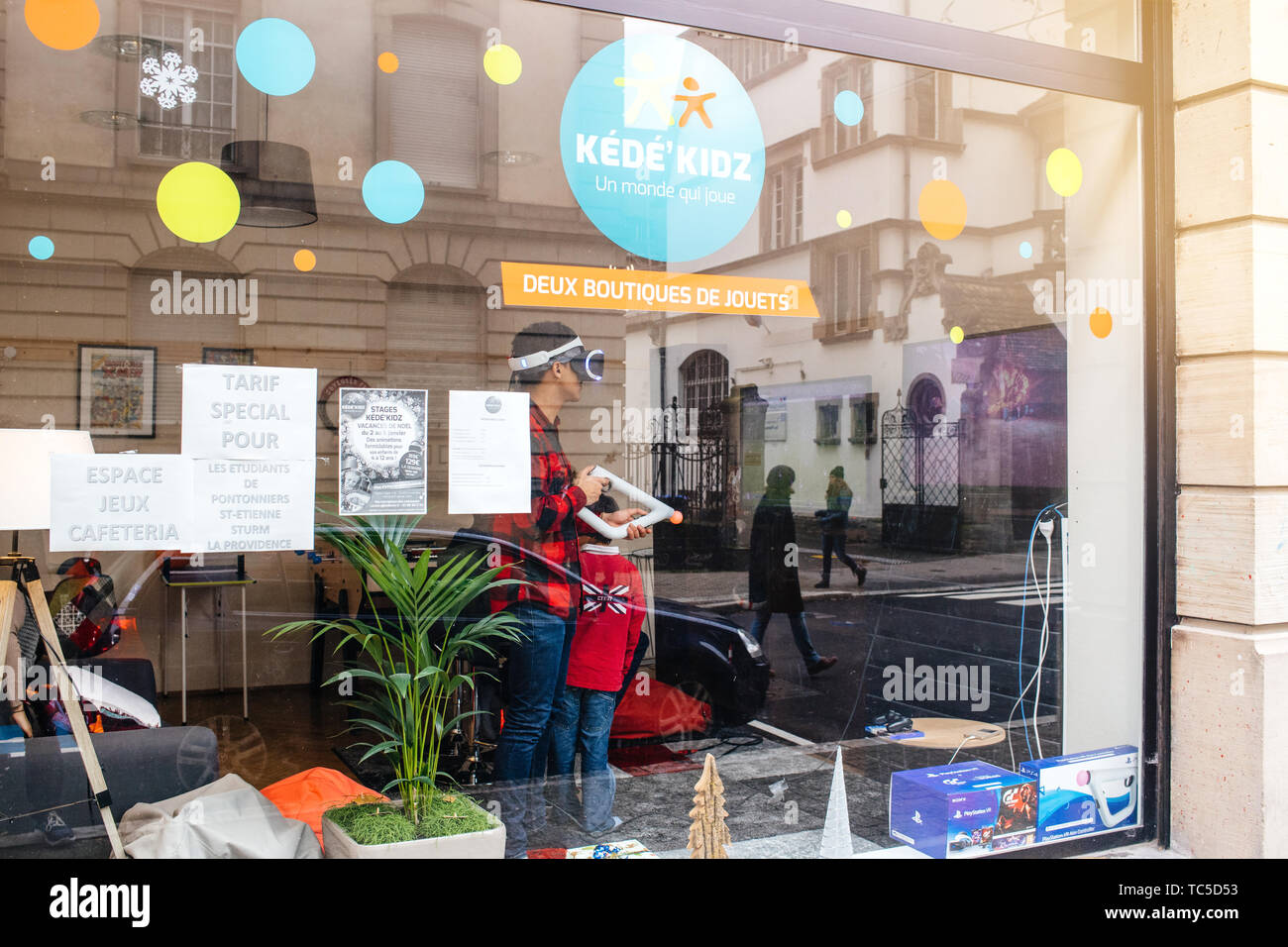 Strasbourg, France - Dec 27, 2017: Man playing inside free game zone with VR set and Precise Aiming for PlayStationVR Aim Controller - Stock Image