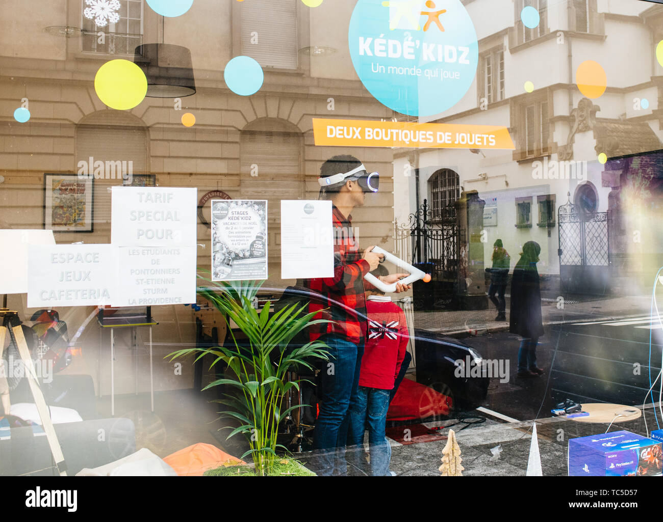 Strasbourg, France - Dec 27, 2017: Man playing inside free game zone with VR set and Precise Aiming for PlayStationVR Aim Controller at the Kede Kidz playing game center - Stock Image