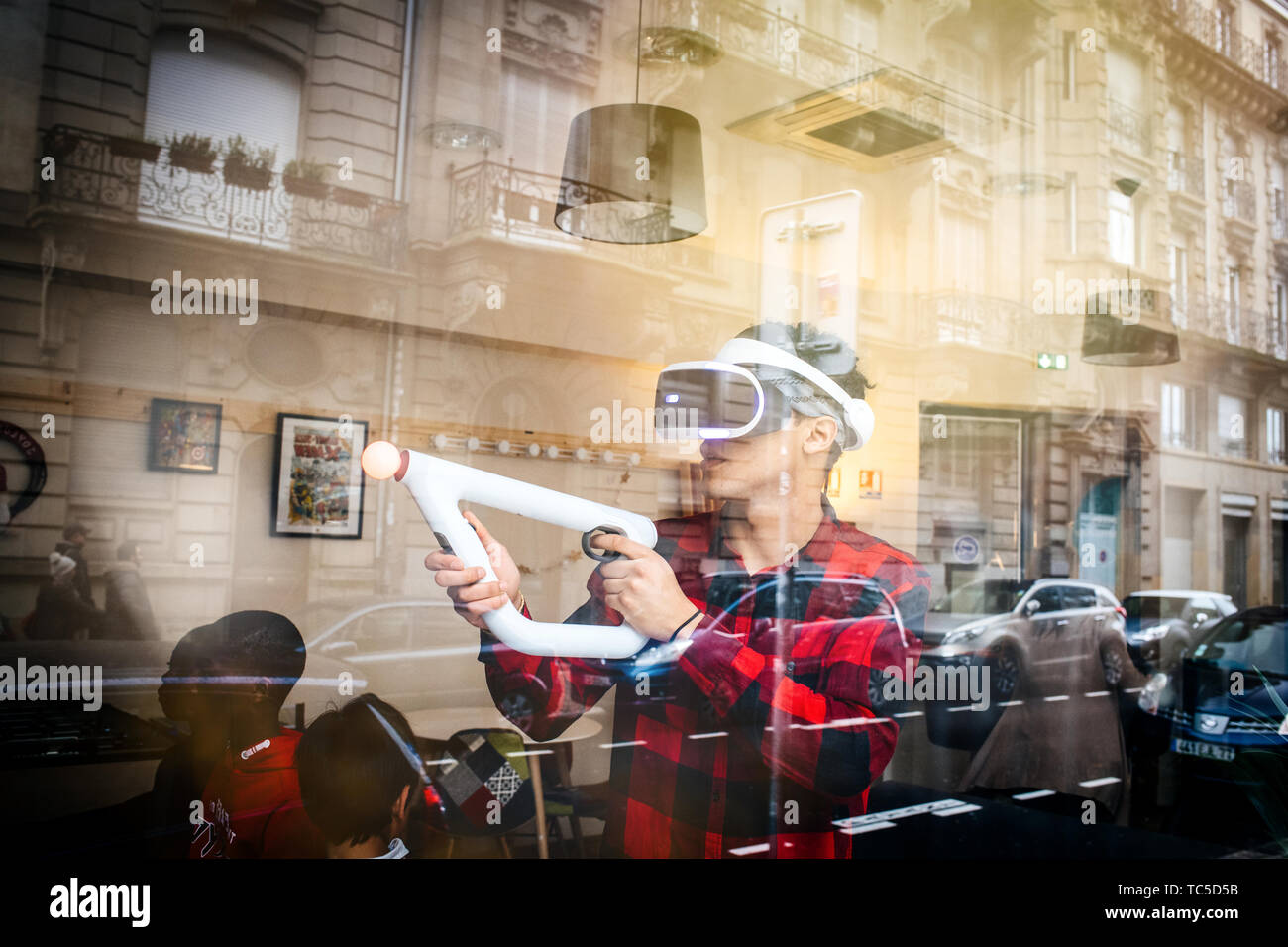 Strasbourg, France - Dec 27, 2017: Man playing inside free game zone with VR set and Precise Aiming for PlayStationVR Aim Controller - city reflection in shwocase window - Stock Image