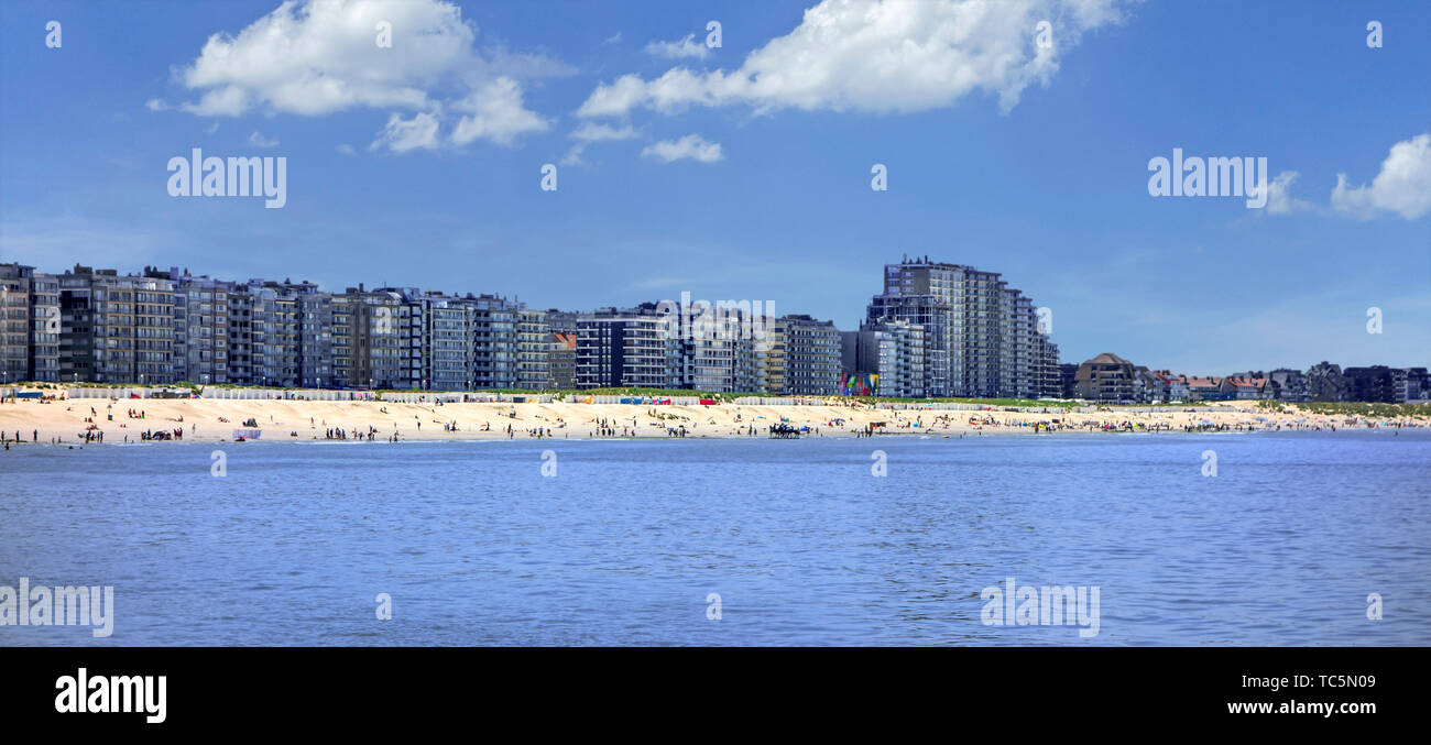 Tourists on the beach and flats and apartments at Nieuport / Nieuwpoort, seaside resort along the North Sea coast, West Flanders, Belgium - Stock Image