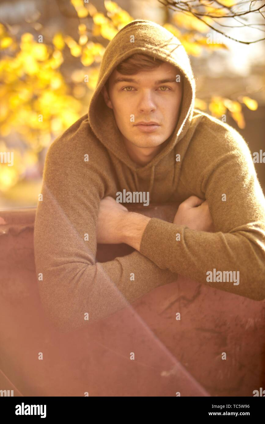 Young man outdoors wearing hoody pullover, autumn, in Munich, Germany - Stock Image