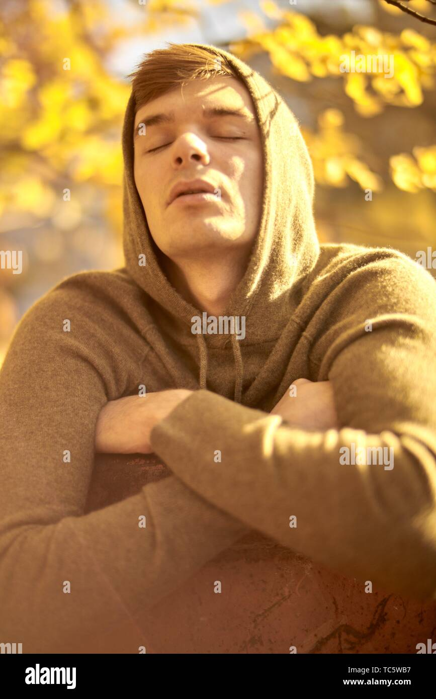 Young emotional man with closed eyes outdoors in autumn, wearing hoody pullover, in Munich, Germany - Stock Image