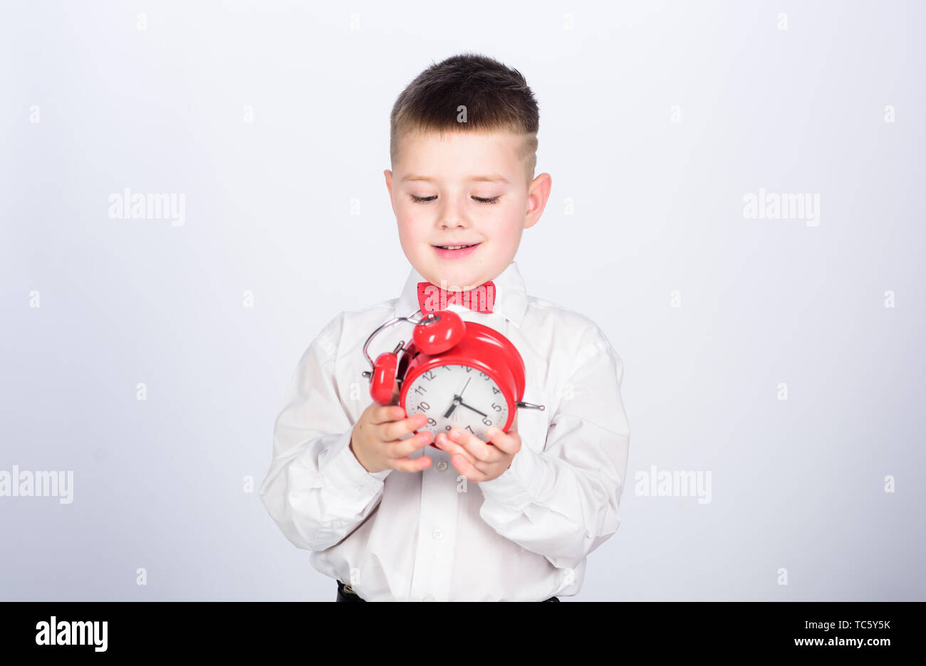 Time management. Morning. Party time. Businessman. Formal wear. tuxedo kid. Happy childhood. little boy with alarm clock. Time to relax. happy child with retro clock in bow tie. Quick chat at morning. - Stock Image