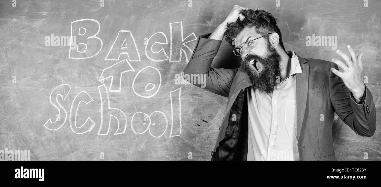 902ee5340 Teacher or educator stands near chalkboard with inscription back to school.  Hate school. Teacher