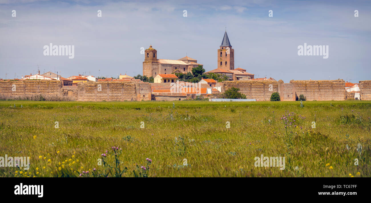 View across fields to to remains of the walls of Madrigal de las Altas Torres, Avila Province, Castile and Leon, Spain.  The church on the left is San Stock Photo