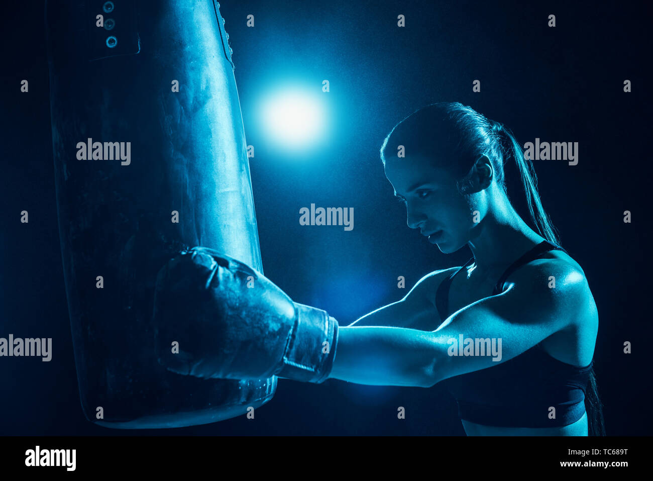 Confident female boxer with ponytail training with punching bag - Stock Image