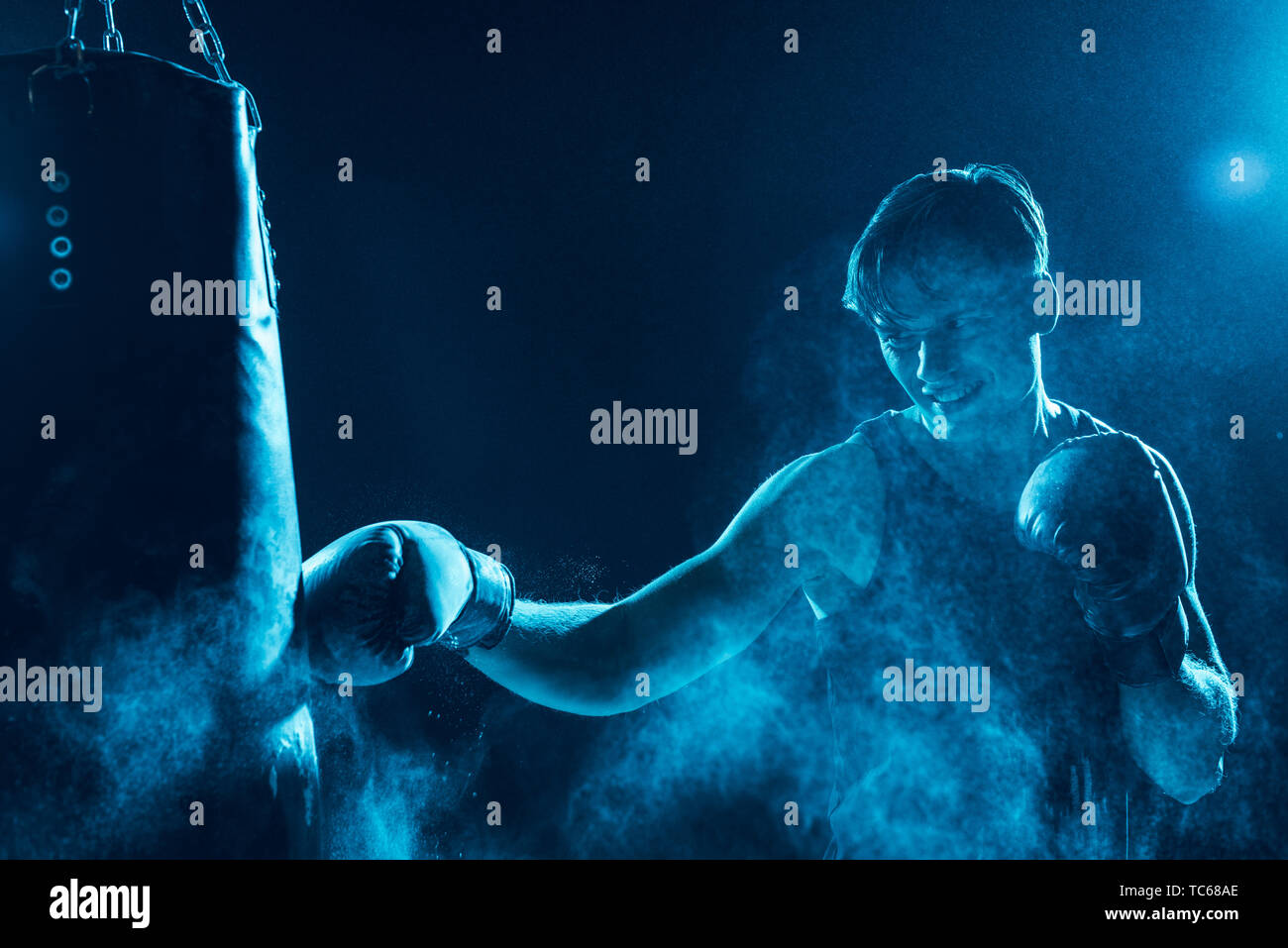 Aggressive boxer in boxing gloves training with punching bag - Stock Image