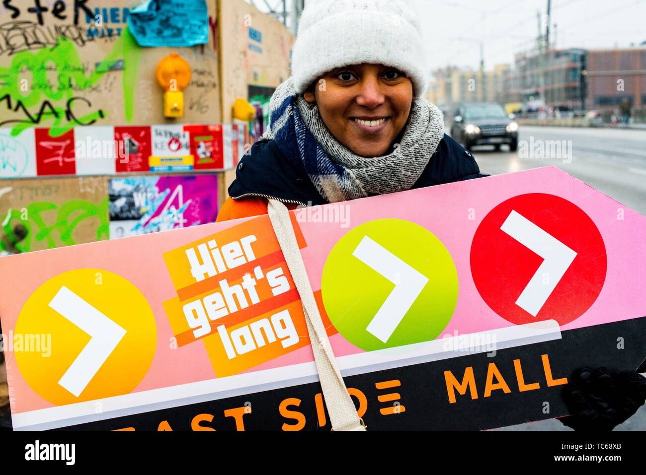 Berlin, Germany. Young Girl attracting attention to East Side Mall shopping center, by standing outside in cold and rainy weather holding a sign, - Stock Image