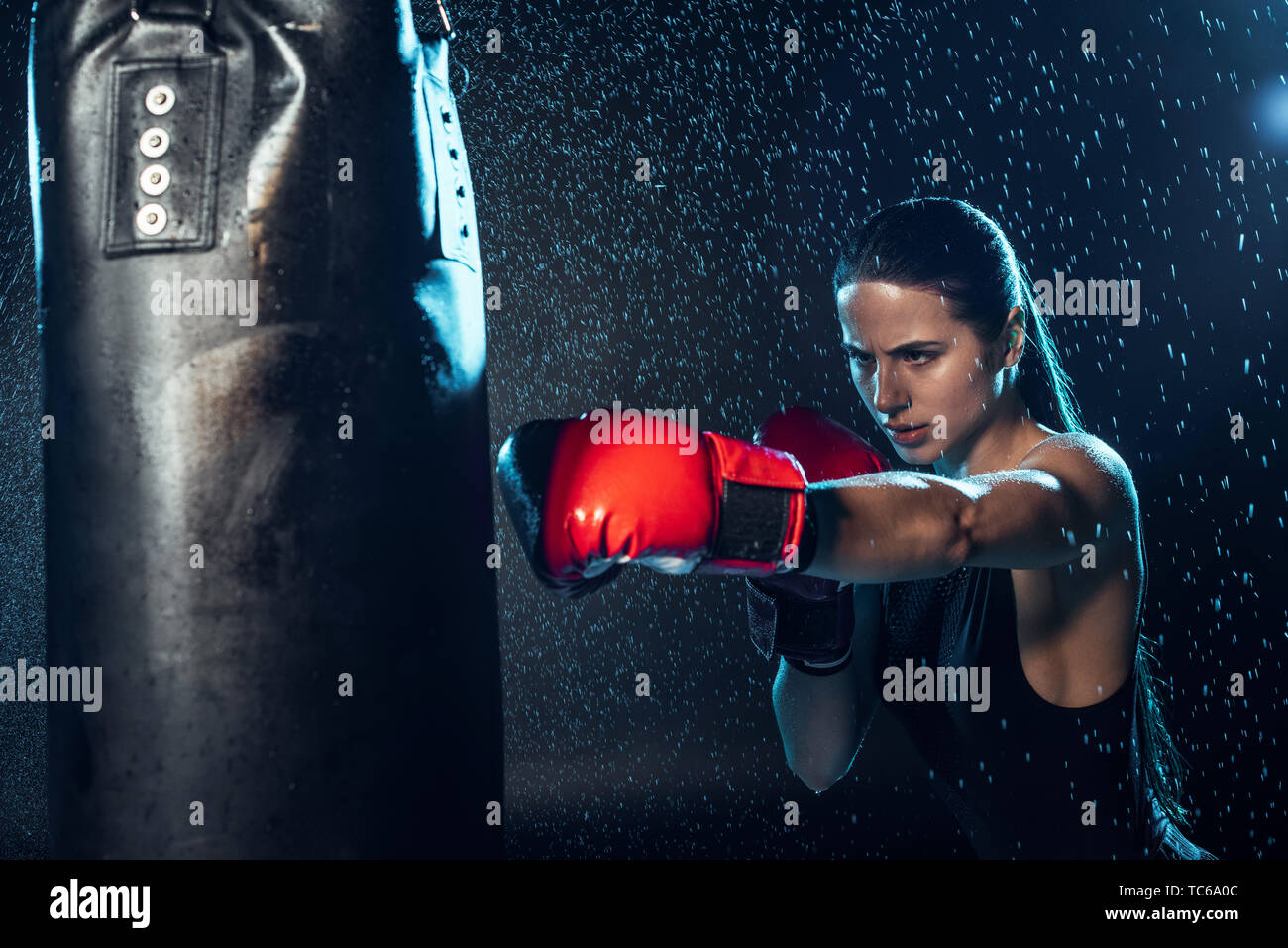 Strong boxer in red boxing gloves training under water drops on black - Stock Image