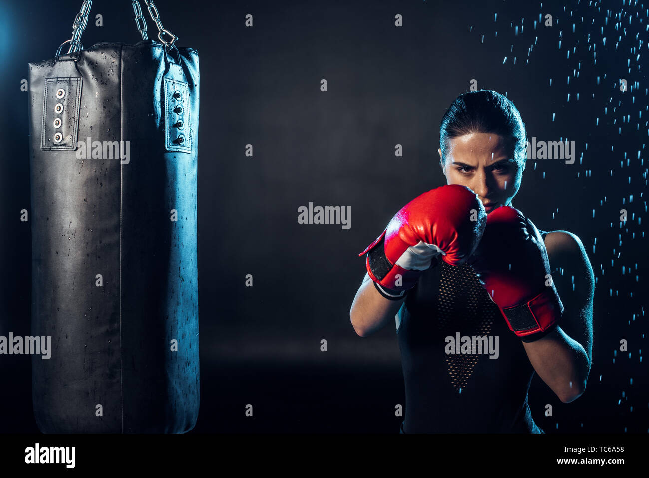 Concentrated boxer in red boxing gloves standing under water drops on black - Stock Image