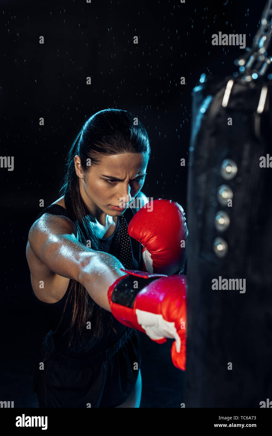 High angle view of pensive boxer in red boxing gloves training under water drops on black - Stock Image