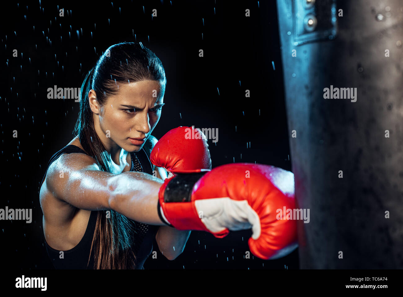 Pensive boxer in red boxing gloves training under water drops on black - Stock Image