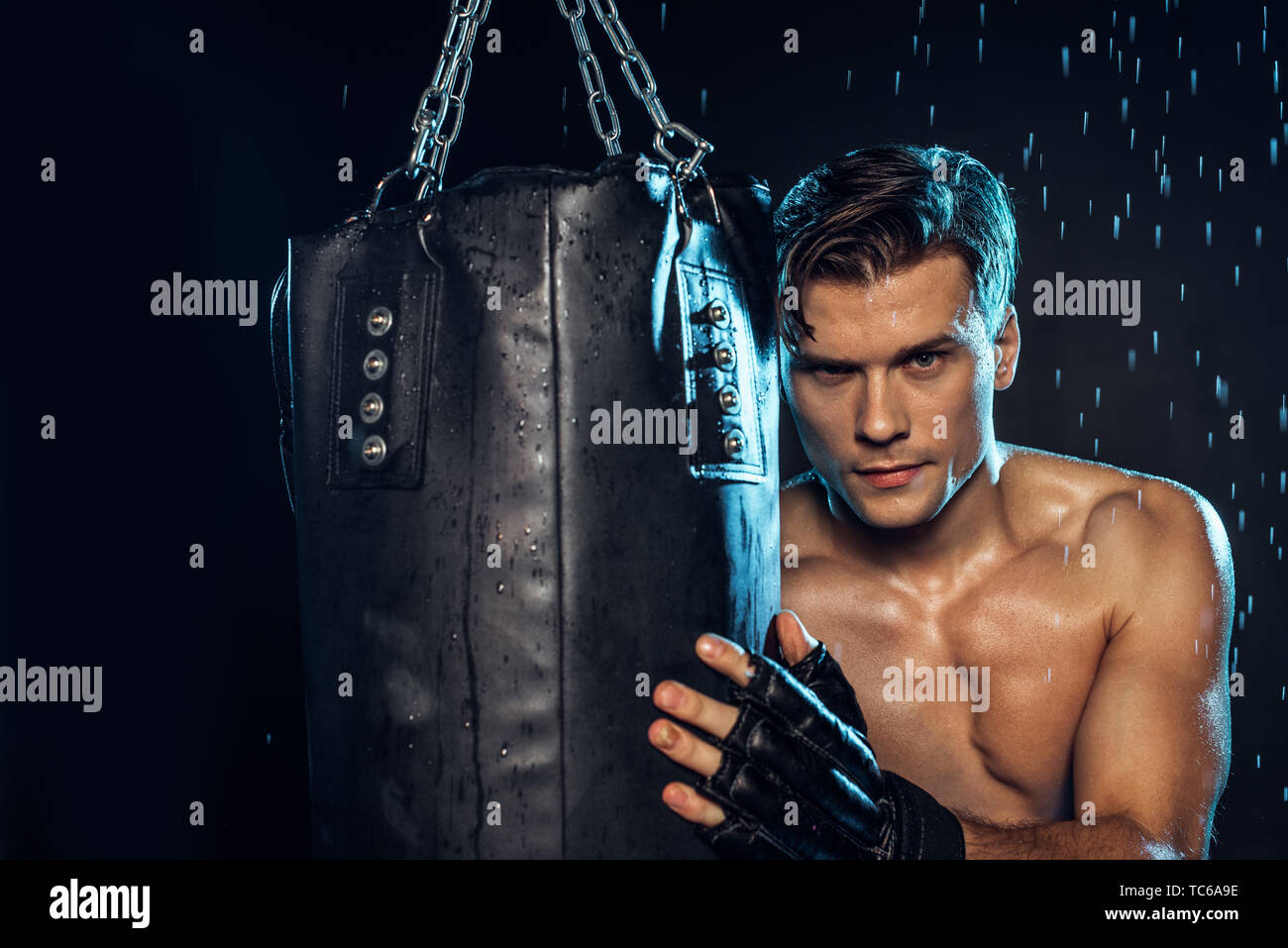 Boxer holding punching bag and looking at camera on black - Stock Image