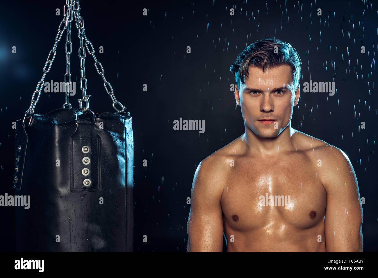 Front view of boxer standing near punching bag under water drops on black - Stock Image