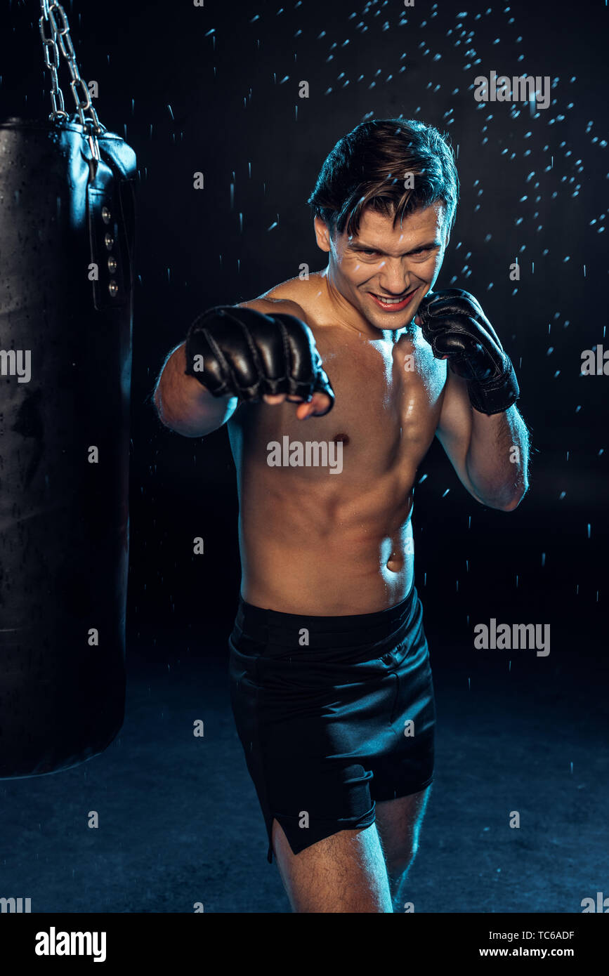 Smiling boxer in gloves standing near punching bag under water drops on black - Stock Image