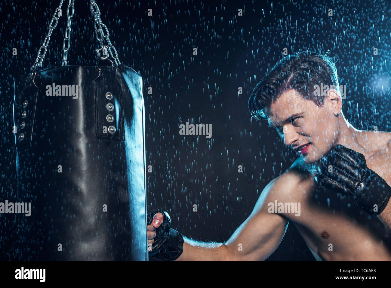Boxer training with punching bag under water drops on black - Stock Image
