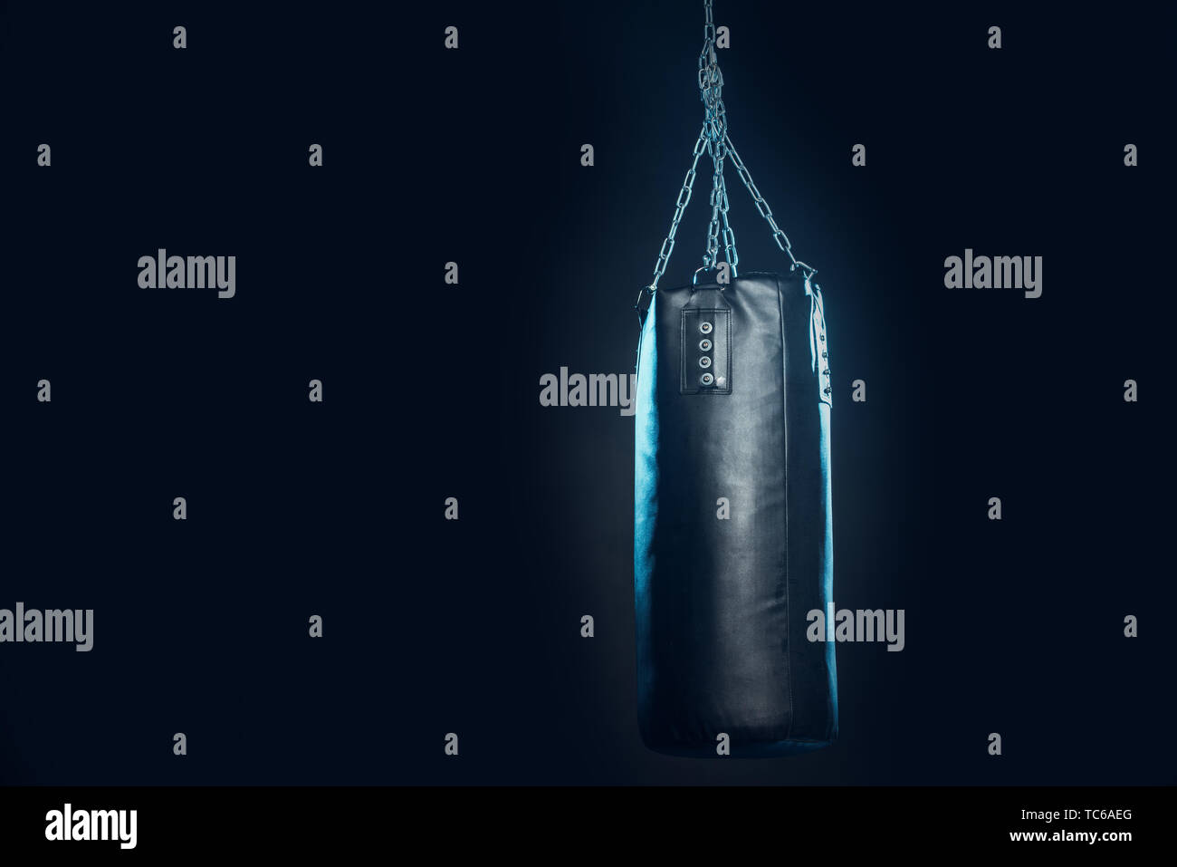 Leather punching bag hanging on steel chains on black - Stock Image
