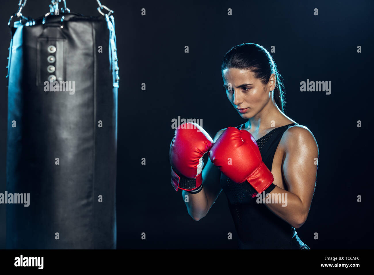 confident boxer in red gloves looking at punching bag on black - Stock Image